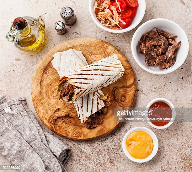 doner kebab grilled meat and vegetables on stone textured backgr - doner kebab stock photos and pictures