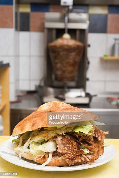 A doner kebab with meat on spit in background