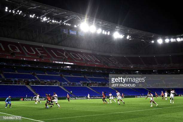 Donetsk and Lyon players run on the pitch with an empty grandstand in background during their UEFA Champions League Group F football match Olympique...