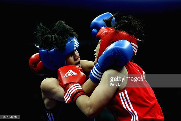 Dong Cheng of China competes against Kum Ju Yun of North Korea in the Women's 5760kg Semifinal at Foshan Gynasium during day twelve of the 16th Asian...