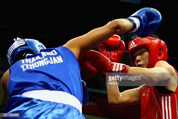 Dong Cheng of China competes with Tassamalee Thongjan of Thailand in the Women's 5760kg Gold Medal match at Foshan Gynasium during day fourteen of...