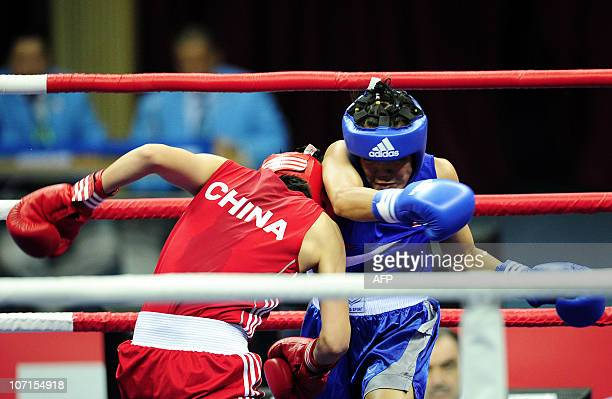 Dong Cheng of China competes with Tassamalee Thongjan of Thailand during the women's 5760kg boxing final competition at the 16th Asian Games in...