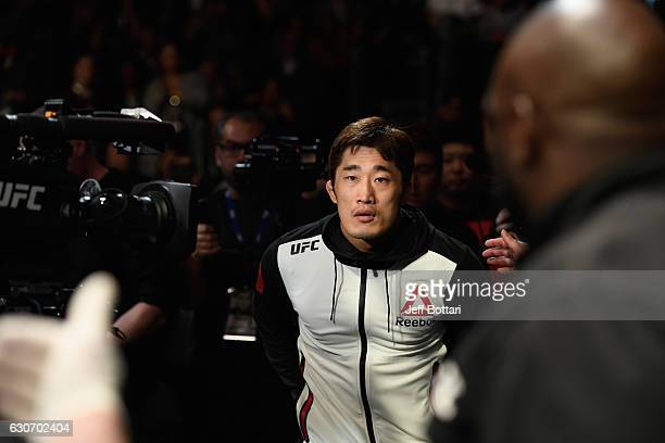 Dong Hyun Kim of South Korea prepares to enter the Octagon to face Tarec Saffiedine of Belgium in their welterweight bout during the UFC 207 event at...