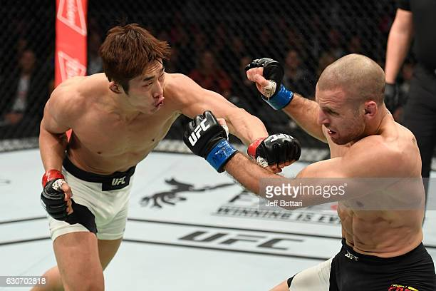 Dong Hyun Kim of South Korea punches Tarec Saffiedine of Belgium in their welterweight bout during the UFC 207 event at T-Mobile Arena on December...