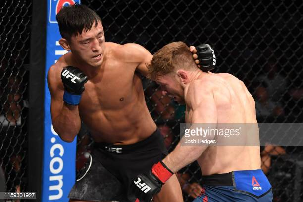 Dong Hyun Ma of South Korea punches Scott Holtzman in their lightweight bout during the UFC Fight Night event at the Prudential Center on August 3,...