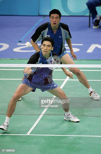 Dong Moon Kim hits the shuttlecock in front of teammate Tae Kwon Ha of Korea in the men's doubles badminton semifinal match against Eng Hian and...