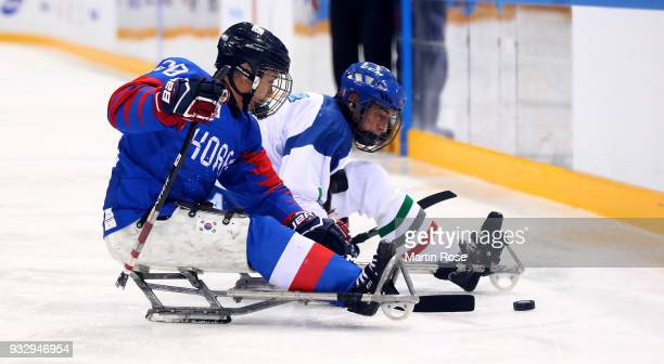Dong Shin Jang of Korea battles for the puck with Florian Planker of Italy in the Ice Hockey bronze medal game between Korea and Italy during day...