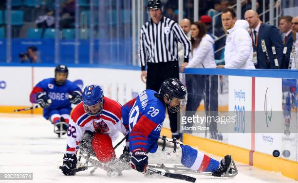 Dong Shin Jang of Korea battles for the puck with Zdenek Habl of Czech Republic in the Ice Hockey Preliminary Round Group B game between Korea and...