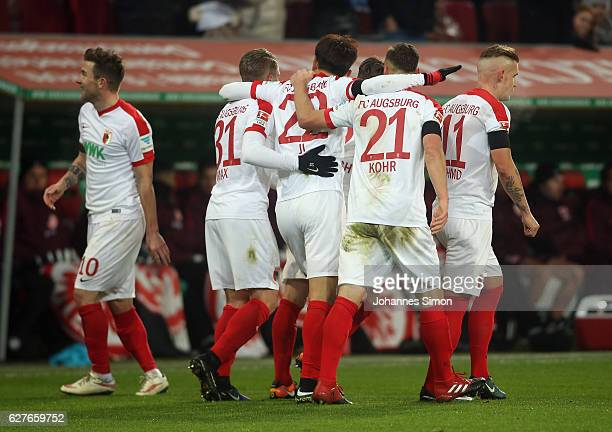 Dong Won Ji of Augsburg celebrates with team mates after scoring his team's first goal during the Bundesliga match between FC Augsburg and Eintracht...