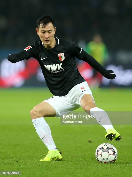 Dong Won Ji of Augsburg runs with the ball during the Bundesliga match between Hertha BSC and FC Augsburg at Olympiastadion on December 18 2018 in...