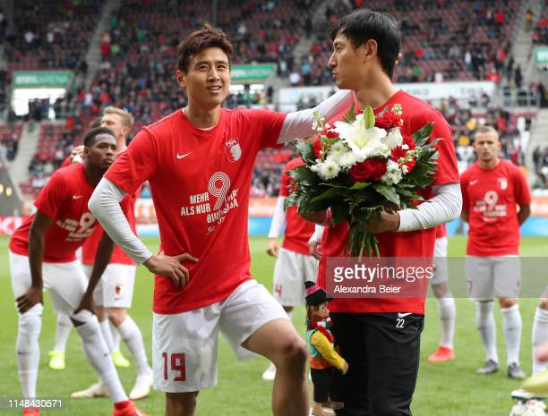 Dong Won Ji of FC Augsburg chats with his teammate JaCheol Koo as Ji is honoured before the Bundesliga match between FC Augsburg and Hertha BSC at...