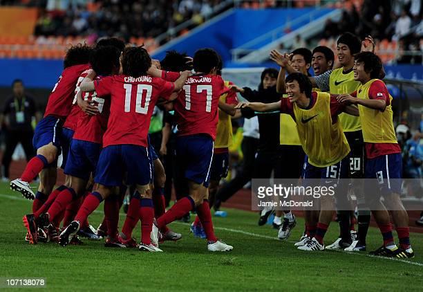 Dong Won Ji of South Korea celebrates scoring the winning goal with team mates of South Korea in the Men's Bronze Medal between South Korea and Iran...