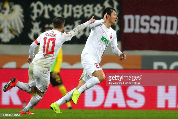 Dong Won Lee of Augsburg celebrates scoring the 2nd team goal with his team mates during the Bundesliga match between FC Augsburg and Borussia...