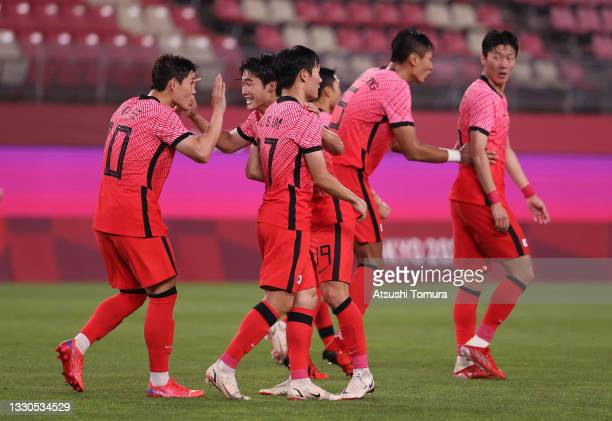 Donggyeong Lee of Team South Korea celebrates with Yoonseong Kang and teammates after scoring their side's second goal during the Men's Group match...