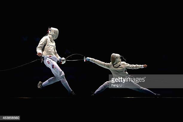 Dongju Kim of Korea and Ivan Ilin of Russia compete in Fencing Mixed Continental Team Gold Medal Bout on day four of the Nanjing 2014 Summer Youth...