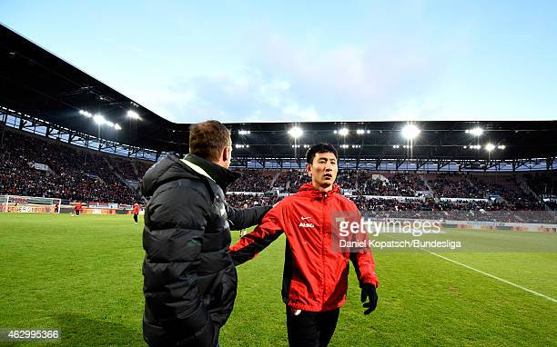 DongWon Ji of Augsburg and Coach Markus Weinzierl of Augsburg react prior to the first Bundesliga match between FC Augsburg and Eintracht Frankfurt...