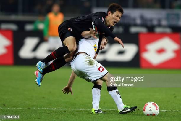 DongWon Ji of Augsburg fouls Tony Jantschke of Moenchengladbach during the Bundesliga match between VfL Borussia Moenchengladbach and FC Augsburg at...