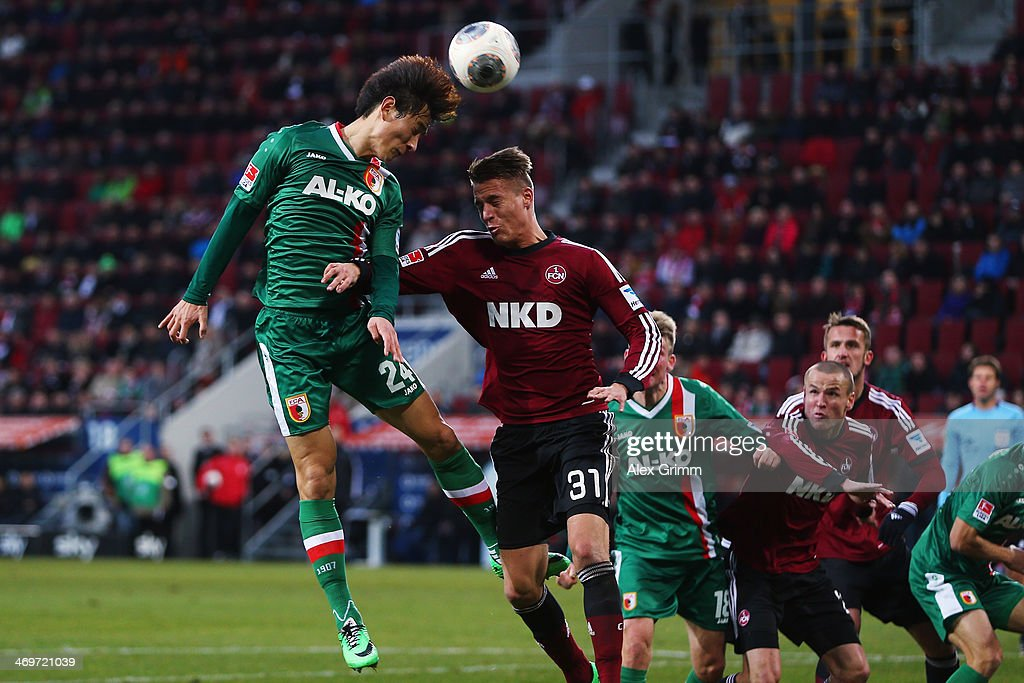 Dong-Won Ji (L) of Augsburg is challenged by Ondrej Petrak of Nuernberg during the Bundesliga match between FC Augsburg and 1. FC Nuernberg at SGL Arena on February 16, 2014 in Augsburg, Germany.