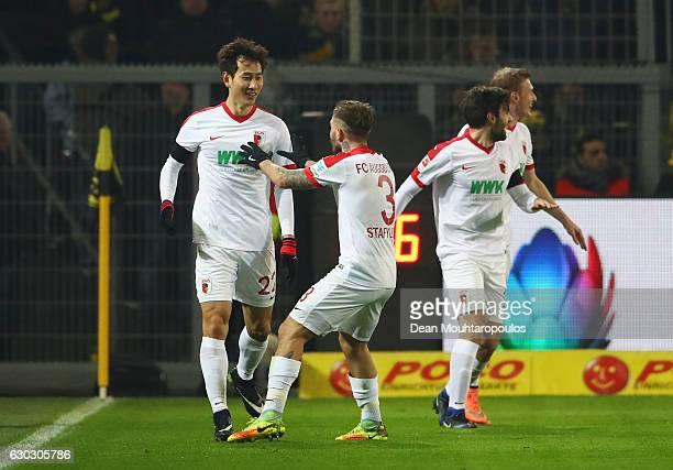 DongWon Ji of FC Augsburg celebrates scoring the opening goal with team mates during the Bundesliga match between Borussia Dortmund and FC Augsburg...