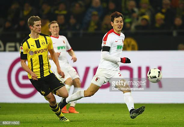 DongWon Ji of FC Augsburg goes past Sven Bender of Borussia Dortmund during the Bundesliga match between Borussia Dortmund and FC Augsburg at Signal...