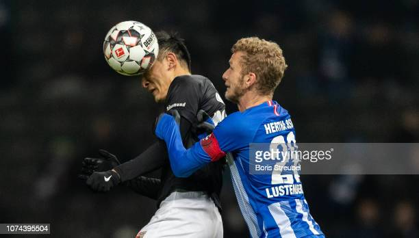 DongWon Ji of FC Augsburg jumps for a header with Fabian Lustenberger of Hertha BSC during the Bundesliga match between Hertha BSC and FC Augsburg at...