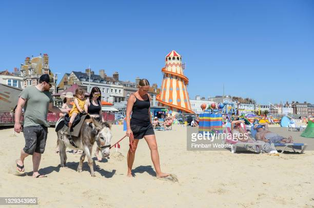 Donkey rides are enjoyed on July 18, 2021 in Weymouth, England. A heat-health warning has been issued for England this weekend, with temperatures are...