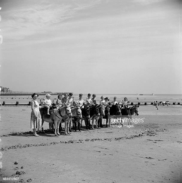 Donkey rides on the beach Bridlington East Riding of Yorkshire 1950s Eleven children enjoy a donkey ride during the summer holidays A mother in...