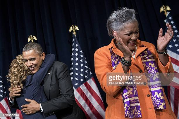Donna Brazile claps while US President Barack Obama hugs Rep Debbie Wasserman Schultz before speaking to the Democratic National Committee at the...