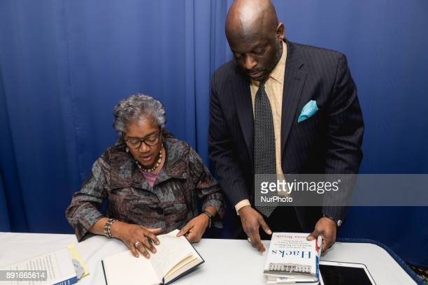 Donna Brazile with Jeff Ballou news editor at Al Jazeera Media Network and the 110th president of the National Press Club by her side signs books for...
