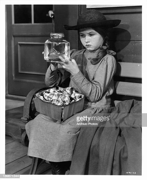 Donna Corcoran sits looking at her goldfish in it's glass jar in a scene from the film 'Scandal At Scourie' 1952