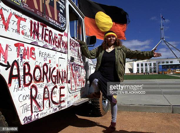 Donna Gibbs an Aborigine from far north state of Queensland flies the Aboriginal flag in front of Parliament House in Canberra 06 April 2000 to...