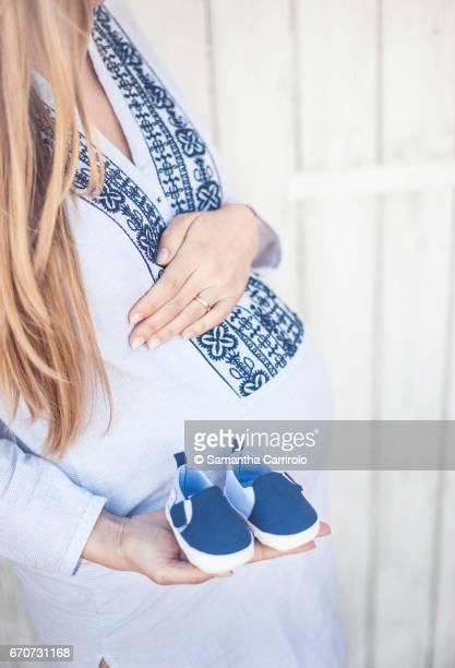 Donna incinta. Mano sul pancione. Camicia a righe con ricamo. Scarpine blu in mano.