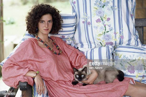 Donna Marella Caraciolo di Castegneto relaxing in a chair with a Siamese cat in her lap at home in Porto Ercole Tuscany Italy in September 1986