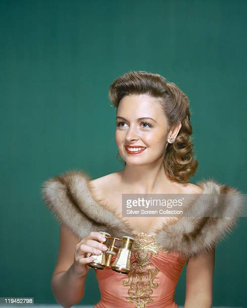 Donna Reed , US actress, wearing a dress with fur trim and holding a pair of opera glasses in a studio portrait, against a petrol blue background,...