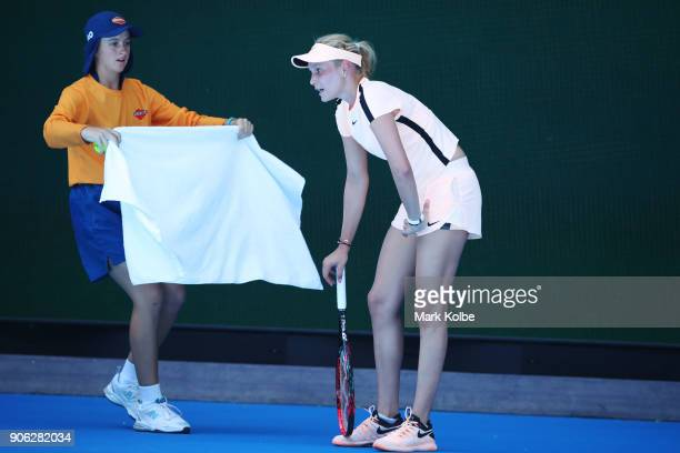 Donna Vekic of Croatia receives a towel from a ball kid in her second round match against Angelique Kerber of Germany on day four of the 2018...