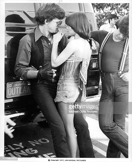 Donna Wilkes putting a cigarette into David Wilson's mouth while John Kirby is looking down in a scene from the film 'Almost Summer' 1978