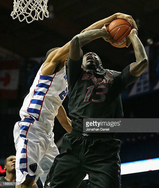 Donnavan Kirk of the DePaul Blue Demons blocks a shot by Cheikh Mbodj of the Cincinnati Bearscats at Allstate Arena on January 15 2013 in Rosemont...