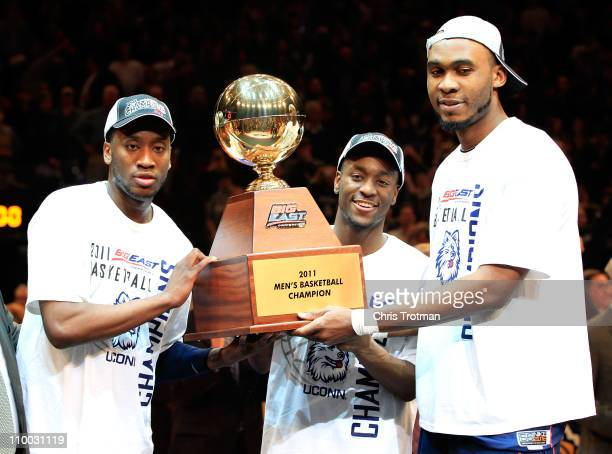 Donnell Beverly, Kemba Walker and Charles Okwandu of the Connecticut Huskies hold up the Championship trophy after defeating the Louisville Cardinals...