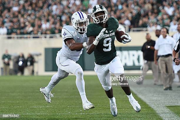 Donnie Corley of the Michigan State Spartans is pursued by Thomas Brown of the Furman Paladins during the first half of a game at Spartan Stadium on...