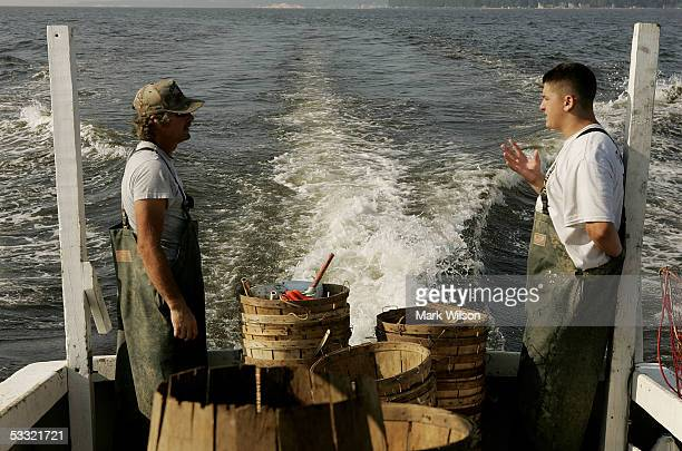 Donnie Eastridge and Kevin Doane aboard the commercial crabbing boat Foxy Roxy get a brief break before pulling up more crab pots on the Chesapeake...