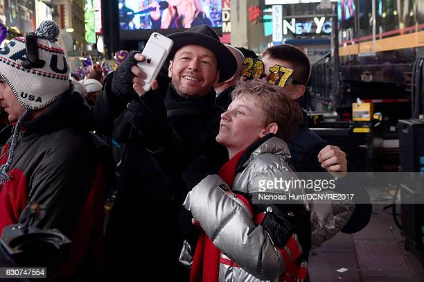 Donnie Wahlberg and Evan Joseph Asher pose for selfies during Dick Clark's New Year's Rockin' Eve 2017 at Times Square on December 31 2016 in New...