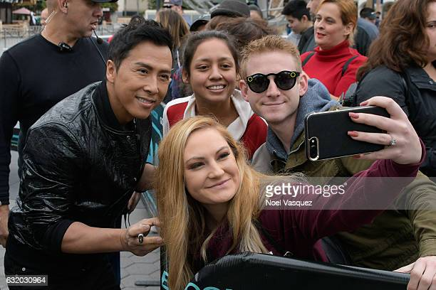 Donnie Yen takes a selfie with fans 'Extra' at Universal Studios Hollywood on January 18 2017 in Universal City California
