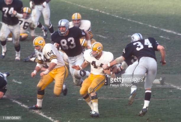 January 14: Donny Anderson of the Green Bay Packers fights off the tackle of Gus Otto of the Oakland Raiders during Super Bowl II on January 14, 1968...