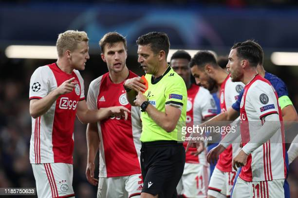 Donny van de Beek and Joel Veltman of AFC Ajax react to Match Referee Gianluca Rocchi as he holds a red card during the UEFA Champions League group H...