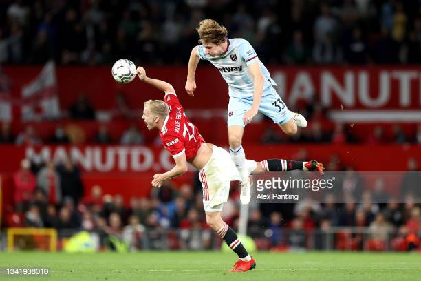 Donny van de Beek of Manchester United jumps for the ball with Alex Kral of West Ham United during the Carabao Cup Third Round match between...