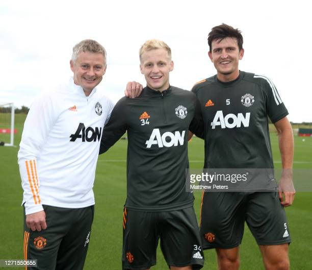 Donny van de Beek of Manchester United poses with Manager Ole Gunnar Solskjaer and Harry Maguire after a first team training session at Aon Training...