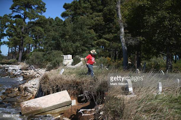 Donny Willey inspects grave markers at the Anchor of Hope Cemetery that is slowly eroding into the Chesapeake Bay October 8 2014 in Hoopers Island...