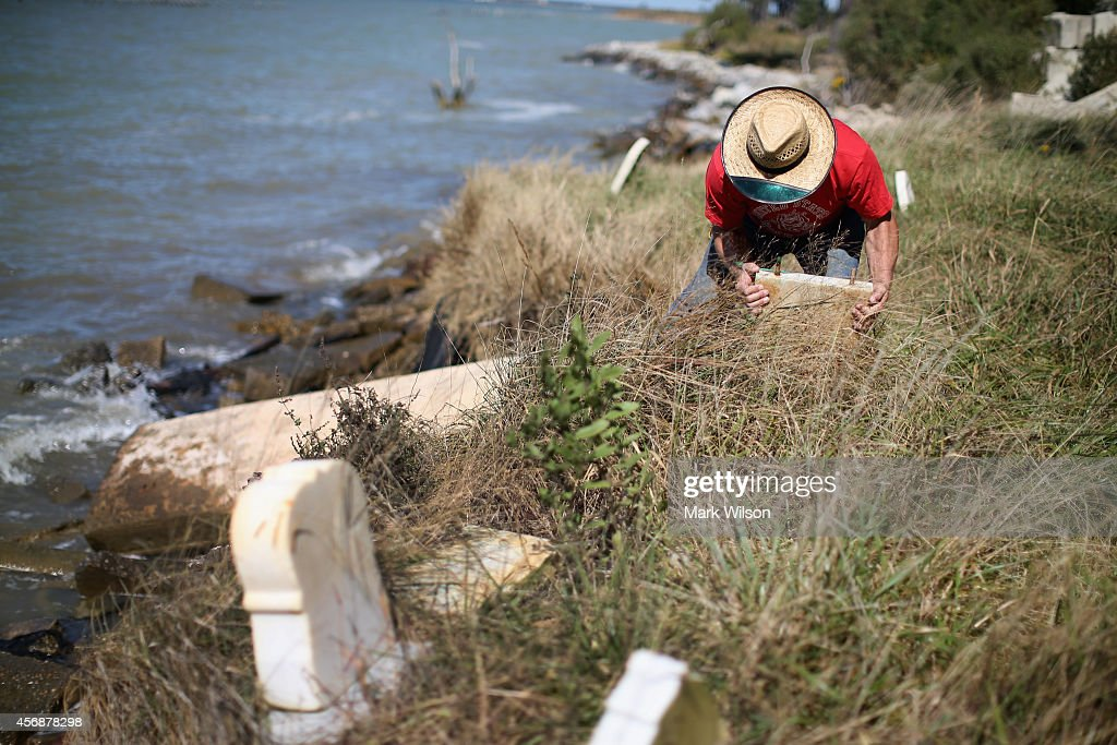 Donny Willey moves back grave markers at the Anchor of Hope Cemetery that is slowly eroding into the Chesapeake Bay. October 8, 2014 in Hoopers Island, Maryland. Willey has volunteered his time to try and save the cemetery from erosion but cannot get a permit from the state of Maryland to erect a seawall. The cemetery is the resting place of more than 150 men, women, and children. Individuals from the War of 1812 to slaves and freed slaves, from the founding family of Hoopers Island to veterans of several wars are buried here. Several islands in the Chesapeake Bay region are slowly eroding away as sea levels are projected to rise several feet over the next century.