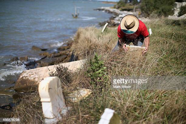 Donny Willey moves back grave markers at the Anchor of Hope Cemetery that is slowly eroding into the Chesapeake Bay October 8 2014 in Hoopers Island...
