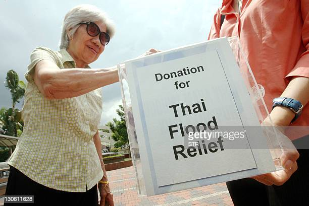 A donor puts money into a donation box for the Thai flood victims at a Buddhist temple in Kuala Lumpur on February 27 2011 Thousands of Bangkok...